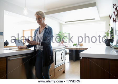 Mature woman working from home, using smart phone and laptop in kitchen - Stock Photo