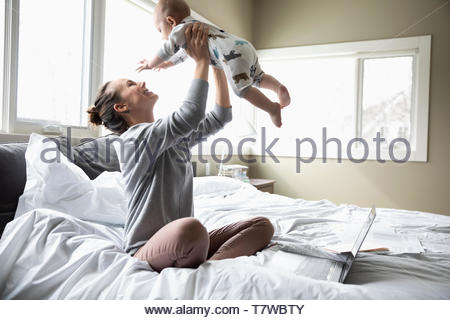Happy mother playing with baby son on bed - Stock Photo