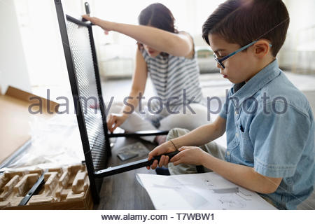 Mother and son assembling flat pack furniture - Stock Photo