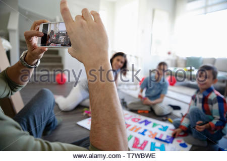 Father photographing family coloring birthday sing in living room - Stock Photo