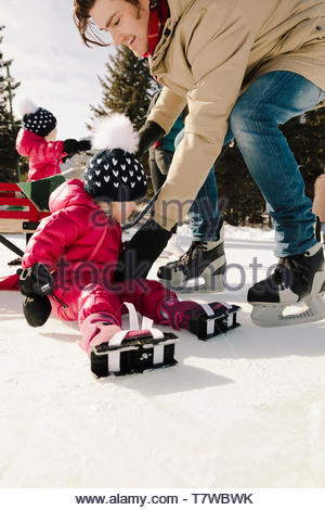 Father helping toddler daughter ice skating - Stock Photo