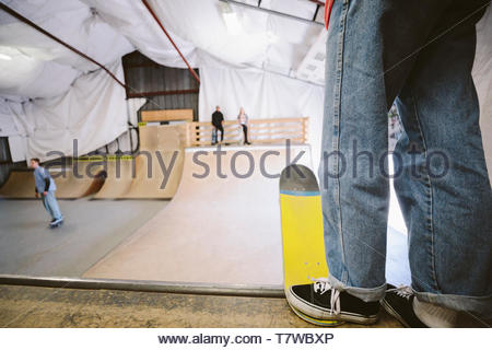 Friends skateboarding at ramp at indoor skate park - Stock Photo