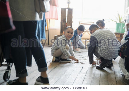 Portrait happy boy playing with dominos on shop floor - Stock Photo