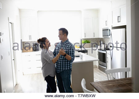 Affectionate couple dancing in kitchen - Stock Photo