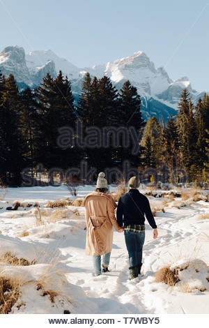 Affectionate young couple walking in snow below mountains - Stock Photo