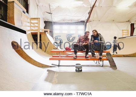 Mature men at indoor skate park, using smart phone - Stock Photo
