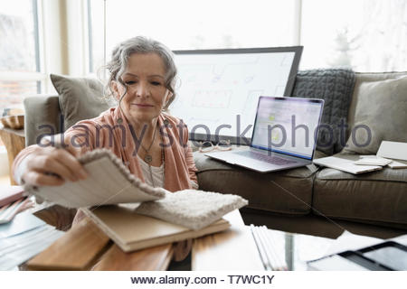Senior female interior designer working from home, viewing swatches in living room - Stock Photo