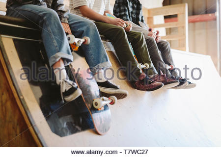 Friends hanging out, sitting at top of ramp at indoor skate park - Stock Photo