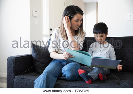 Mother and toddler son reading book on living room sofa - Stock Photo