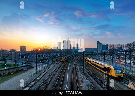 The Hague (Den Haag in Dutch) skyline during the sunset moment behind the train station - Stock Photo
