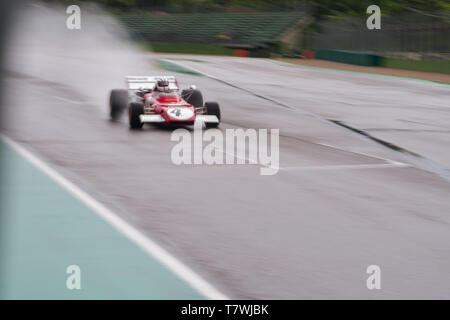 vintage formula one car is flying on a wet track, panning photo - Stock Photo