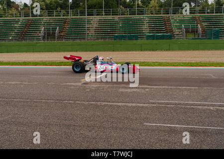 vintage formula one car is flying on a main straight - Stock Photo