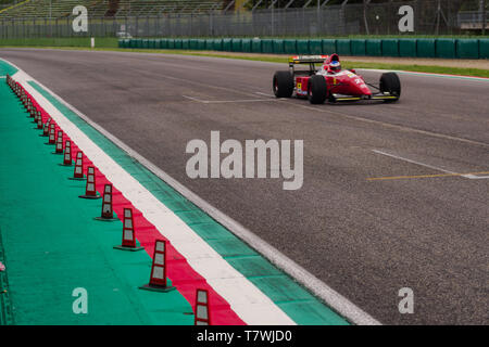 Vintage Ferrari is flying on the main straight of a race track - Stock Photo