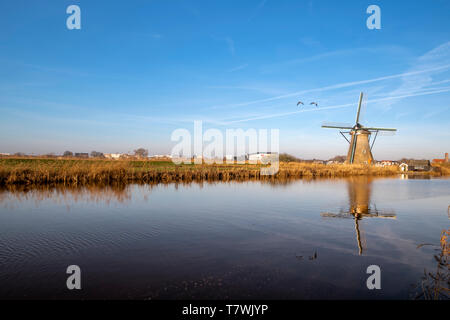 Dutch landscape in the early morning with the windmill reflected on the calm canal at Alblasserdam city near Rotterdam, Netherlands - Stock Photo