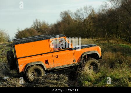 Off-road Landrover tackles a muddy trial course on a Winter's day in the Peak District, Derbyshire - Stock Photo