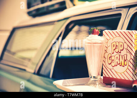 Tray on a 60's car with popcorn and a strawberry milkshake - Stock Photo