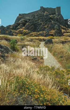 Stone pathway towards castle on top of rocky hill covered by flowers and dry bushes near Monsanto. A cute and peculiar historic village of Portugal. - Stock Photo