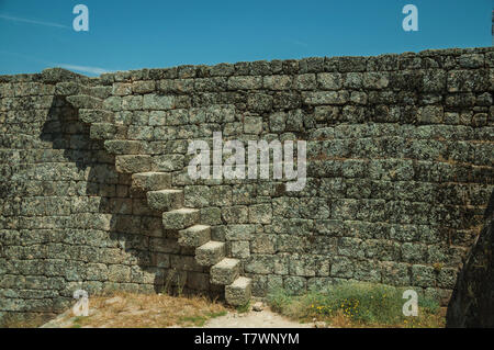 Tall wall with staircase made of stone bricks on top of rocky hill at the Castle of Monsanto. A cute and peculiar historic village of Portugal. - Stock Photo