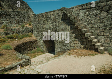 Wall made of stone bricks with staircase and gateway on top of rocky hill at the Castle of Monsanto. A cute and peculiar historic village of Portugal. - Stock Photo