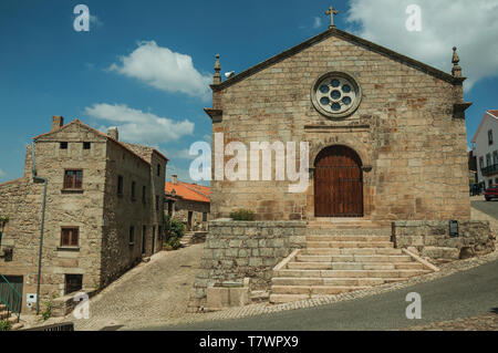 Medieval church with stone wall and wooden door next to old houses in a deserted alley at Monsanto. A cute and peculiar historic village of Portugal. - Stock Photo