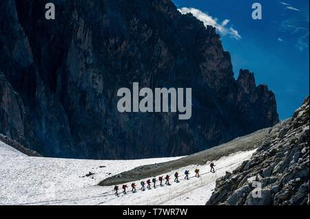 Italy, Courmayeur, Pointe Helbronner, alpinists hiking towards the arrival station of the Panoramic-Mont-Blanc cable-car, linking the Aiguille du Midi to the Pointe Helbronner on the italian side of Mont-Blanc - Stock Photo