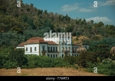 Ruined facade of abandoned building among thicket and grove on a small farm near Monsanto. A cute and peculiar historic village of Portugal. - Stock Photo