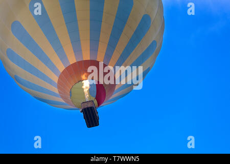 Flight of a balloon in the blue sky, view of the basket overhead - Stock Photo