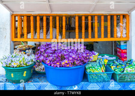 Small stall with flowers and incense stick offerings at the sacred Sri Maha Bodhi Tree in the Mahamewna Gardens, Anuradhapura, Sri Lanka. - Stock Photo