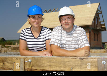Couple wearing hard hats posing over unfinished house - Stock Photo