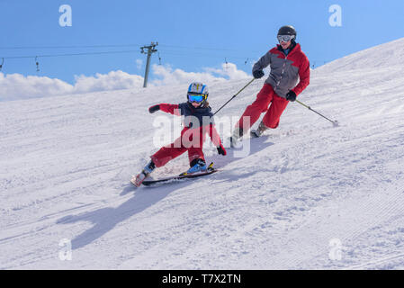 Young boy skiing with his father on good prepared slope - Stock Photo