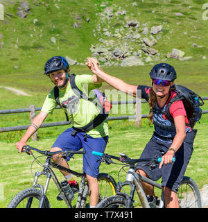 Young couple jubilating on bike, enjoying their fantastic tour in the alps - Stock Photo