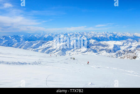 A group of freeriders skiing on the wide glacier area of Monte Rosa with fantastic view to the alps - Stock Photo