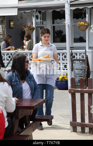 Lyme Regis, Dorset - A waitress serving fish and chips al fresco to customers outside, 2019 - Stock Photo