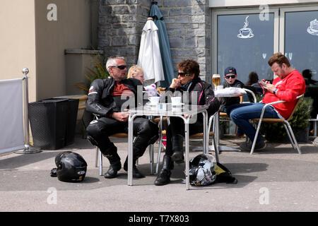 Lyme Regis, Dorset - Two leather clad bikers taking a coffee break outside, al fresco style, in the sunshine - Stock Photo