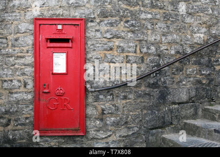 Lyme Regis, Dorset, UK - Classic Red Letterbox mounted against brick wall with copyspace - Stock Photo