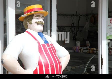 Lyme Regis, Dorset - Antique, life size, jolly butcher statue standing outside butchers shop in the daytime - Stock Photo