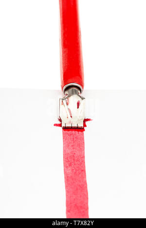 red dip pen draws a red line on sheet of paper by wide nib close up isolated on white background - Stock Photo