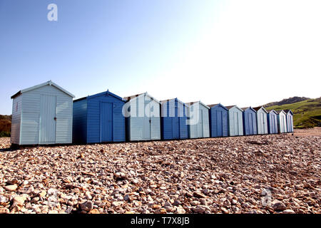 Charmouth Beach, Dorset, UK - Wooden beach Huts on pebble beach at Charmouth with blue sky in background - Stock Photo