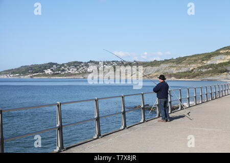 Charmouth, Dorset, UK - Man fishing at the coast on a sunny day with Lyme Regis in distance, 2019 - Stock Photo