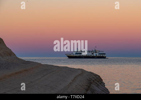 The Lindblad National Geographic Venture anchored at sunset off the shore of Isla San Jose, Baja California Sur, Mexico. - Stock Photo