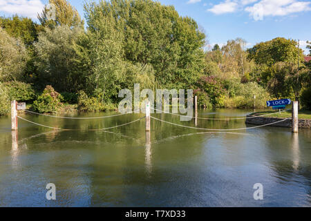 Ropes bar entry to a mill stream to ensure boats take the right entrance to Iffley Lock on the Thames, in the warm autumn sunlight, Oxford, UK - Stock Photo