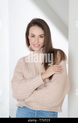 Smiling woman in beige sweater - Stock Photo