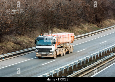 Small Cistern truck on country highway under a beautiful sky - Stock Photo
