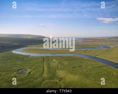 Beautiful aerial drone landscape image of meandering river through marshland at sunrise - Stock Photo