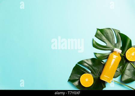 Orange juice in glass bottle on a sheet of a tropical plant bright blue background. Healthy eating concept. Minimalism. - Stock Photo