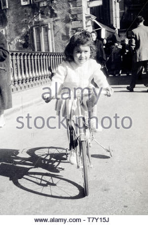 girl riding a bicycle with extra wheel support France 1958 - Stock Photo