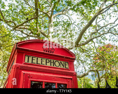 Red telephone box at Brunswick Square Gardens, Camden, London. - Stock Photo