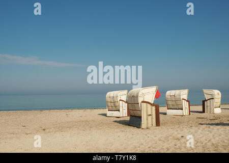 four empty roofed wicker beach chairs on a deserted  sandy beach under blue sky  in Germany - Stock Photo