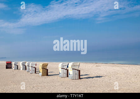 numerous roofed wicker beach chairs on a deserted sandy beach under blue sky in Germany - Stock Photo
