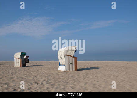 two roofed wicker beach chairs under blue sky on a deserted sandy beach of the Baltic Sea in Germany - Stock Photo